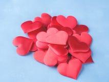 Rode harten op geweven blauwe achtergrond Stock Afbeeldingen