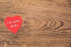 Rode hartpost-it met de tekst 'Ich liebe dich 'op een houten achtergrond Vertaling: 'I-liefde u ' stock foto's