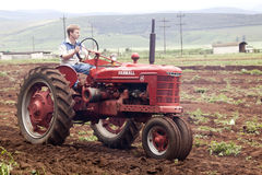 Rode Herstelde Uitstekende Tractor die Landbouwgebied ploegen Stock Foto's