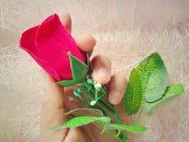 Rode het flanel nam bloem, in linkerhand, vezelachtergrond toe royalty-vrije stock fotografie