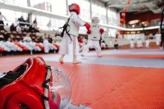 Rode het vechten helm met duidelijk plastic masker op de vloer bij voorgrond Twee jongens in kimono op achtergrond in karate best stock foto's