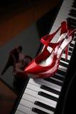 Rode hoge hielschoenen op piano Stock Afbeeldingen