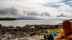 Rode hoofdvrouwen die het overzees in Schotland bekijken royalty-vrije stock fotografie