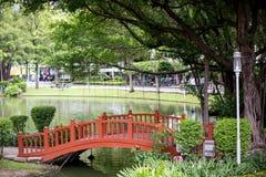 Rode houten brug voor kruis de sloot in openbaar park Het schaduwrijke park met het verfrissen van paraplu's royalty-vrije stock fotografie