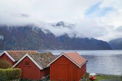 Rode houten cabines langs fjord in Noorwegen dichtbij Flam stock foto