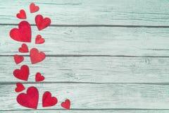Rode houten harten op de linkergrens op een groene houten achtergrond Stock Foto