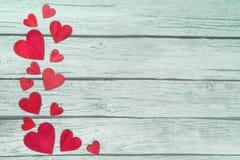Rode houten harten op de linkergrens op een groene houten achtergrond Stock Fotografie