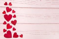 Rode houten harten op de linkergrens op een roze houten achtergrond Stock Afbeelding