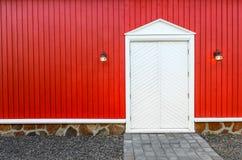 Rode houten muur en witte voordeuren met twee lampen Stock Fotografie