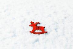 Rode houten stuk speelgoed herten in de sneeuw Stock Fotografie