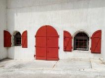 Rode ijzerdeuren en vensters met blinden in een oud huis stock foto's