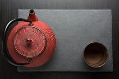 Rode ijzertheepot op donkere kleurenachtergrond stock afbeeldingen
