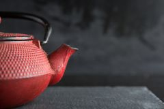 Rode ijzertheepot op donkere kleurenachtergrond stock foto's