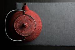 Rode ijzertheepot op donkere kleurenachtergrond royalty-vrije stock foto's