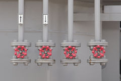 Rode industriële kleppen op een rij op grijs pijpleidingensysteem stock fotografie