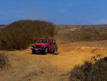 Rode Jeep die door ruwe weg gaan Stock Afbeeldingen