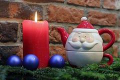 Rode kaars, blauwe Kerstmisballen en Santa Claus-theepot Royalty-vrije Stock Afbeelding