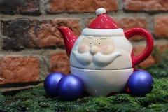 Rode kaars, blauwe Kerstmisballen en Santa Claus-theepot Royalty-vrije Stock Afbeeldingen