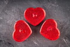 Rode kaarsen in de vorm van harten op een grijze achtergrond Het symbool van de dag van minnaars De dag van de valentijnskaart Co Royalty-vrije Stock Foto