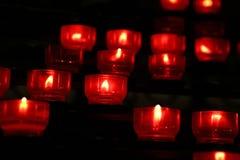 Rode kaarsen die in donkere kerk zich dicht opbranden Stock Foto's