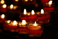 Rode kaarsen die in donkere kerk zich dicht opbranden Royalty-vrije Stock Foto's