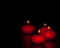 Rode kaarsen met vlam op houten en zwarte achtergrond, donkere atmospere Stock Afbeeldingen