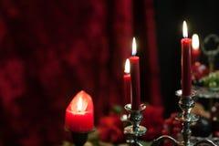 Rode kaarsen op een rode fluweelachtergrond Royalty-vrije Stock Afbeeldingen