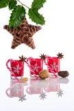 Rode kaarshouders met kristalsneeuwvlokken, suikerrieten, anijsplantsterren, noten, heilige die en denneappelster op weerspiegele Royalty-vrije Stock Afbeeldingen