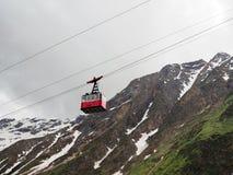 Rode kabelwagen op de achtergrond van de bergen Oude rode kabelwagen bij berg royalty-vrije stock afbeeldingen