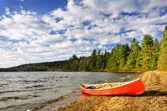 Rode kano op meerkust royalty-vrije stock afbeeldingen