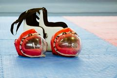 Rode karate twee het vechten helm met duidelijke plastic maskers en twee lichaams beschermende vesten op de vloer stock foto