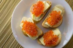 Rode kaviaar op brood en boterclose-up, vier sandwiches op witte plaat Mening van hierboven royalty-vrije stock afbeelding