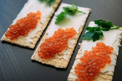 Rode kaviaar op knapperig brood met roomkaas en groen Gezond voedsel Sandwiches met kaviaar op zwarte achtergrond wordt ge?soleer stock afbeelding
