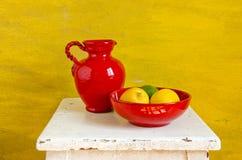 Rode keramiekkruik en plaat met citroenen stock afbeelding
