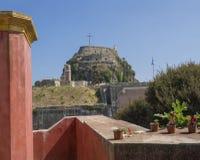 Rode kerkmuur met mening over Beroemde toeristische oriëntatiepunt oude Venetiaanse vesting met klokketoren, Kerkyra-stad, Korfu royalty-vrije stock afbeeldingen