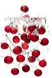 Rode kersen die in water vallen Stock Afbeeldingen