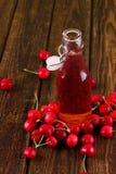 Rode kersendrank in fles in het midden van fruit Stock Fotografie