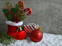 Rode Kerstman` s laars met sparrentak, de decoratieve bladeren van de hulstbes, suikergoedriet en rode Kerstmisbal Royalty-vrije Stock Foto