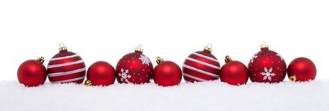 Rode Kerstmis grote en kleine die ballen op sneeuw worden geïsoleerd stock afbeeldingen