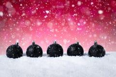 Rode Kerstmisachtergrond - Verfraaide Zwarte Ballen op Sneeuw met sneeuwvlokken en sterren Royalty-vrije Stock Afbeeldingen