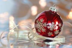 Rode Kerstmisbal met bezinning tegen een lichtblauwe achtergrond Stock Fotografie