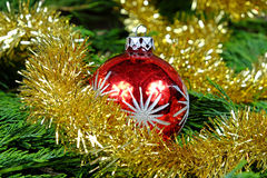 Rode Kerstmisbal met zilveren sterren rond haar Kerstmisketen in gouden kleur Royalty-vrije Stock Afbeeldingen