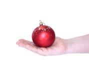 Rode Kerstmisbal in vrouwelijke geïsoleerde hand Stock Afbeeldingen
