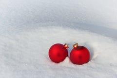 Rode Kerstmisballen in de Sneeuw Stock Afbeeldingen