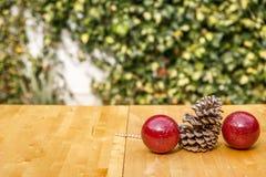 Rode Kerstmisballen en een pinecone op een houten lijst Royalty-vrije Stock Fotografie
