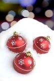 Rode Kerstmisballen met geschilderde sneeuwvlokken die in sneeuwbank liggen Royalty-vrije Stock Afbeeldingen