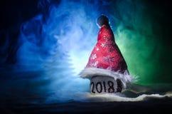 Rode Kerstmisballen met het aantal van 2018 en de hoed van de Kerstman op natuurlijke sneeuwachtergrond Gelukkig Nieuwjaar 2018 c Royalty-vrije Stock Afbeelding