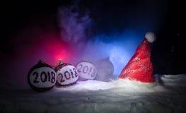 Rode Kerstmisballen met het aantal van 2018 en de hoed van de Kerstman op natuurlijke sneeuwachtergrond Gelukkig Nieuwjaar 2018 c Royalty-vrije Stock Foto's
