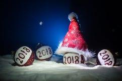 Rode Kerstmisballen met het aantal van 2018 en de hoed van de Kerstman op natuurlijke sneeuwachtergrond Gelukkig Nieuwjaar 2018 c Stock Afbeeldingen