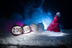Rode Kerstmisballen met het aantal van 2018 en de hoed van de Kerstman op natuurlijke sneeuwachtergrond Gelukkig Nieuwjaar 2018 c Stock Afbeelding